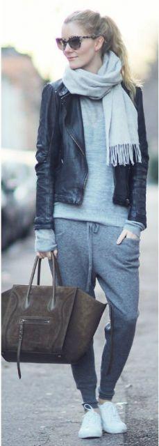 Modelo veste calça moletom cinza, blusa e cachecol na mesma cor e jaqueta preta, tênis branco e bolsa de mão marrom.