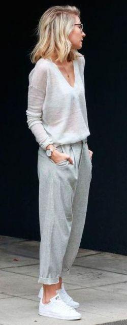 Look com calça moletom feminina na cor cinza, blusa fluída e tênis branco.