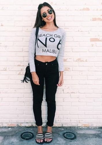 Modelo veste blusa cropped cinza, calça jeans preta e chinelo slide estampado.