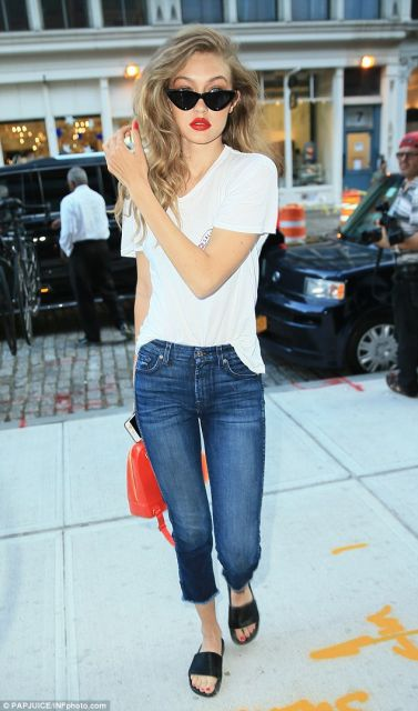 Gigi Hadid veste calça jeans azul, blusa branca básica e chinelo slide preto.
