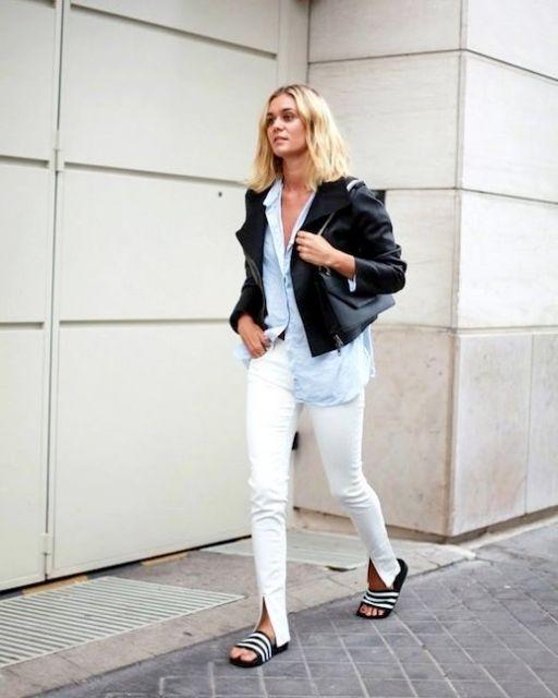 Modelo veste calça jeans branca, camisa, jaqueta de couro preta e chinelo slide estampado.