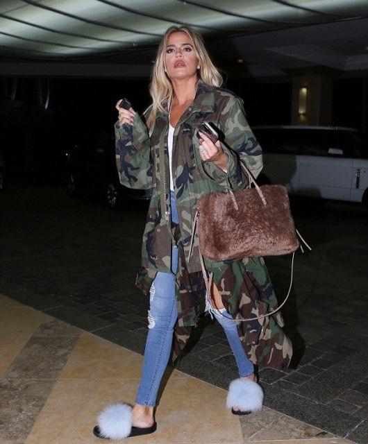 Khloe Kadarshian veste calça jeans azul destroyed, casaco longo estampa camuflada, chinelo slide azul de pelinhos e bolsa marrom.