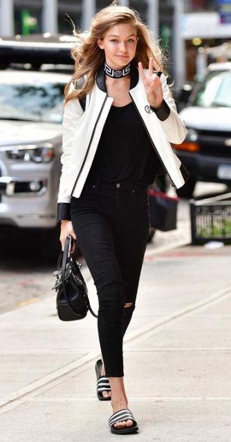 Gigi Hadid veste calça preta rasgad no joelho, blusa preta, jaqueta branca, chinelo slide preto com listras e bolsa de mão