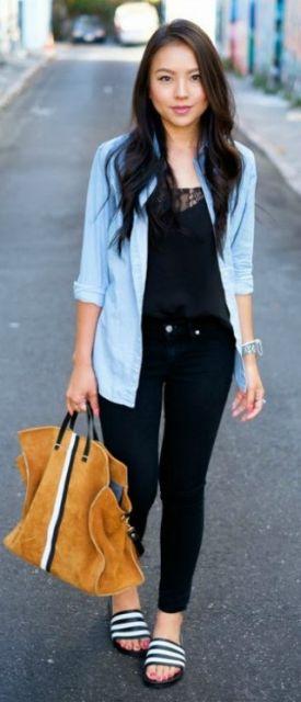Modelo veste calça jeans escura, blusa preta com sobreposição azul, chinelo slide na cor preta e bolsa camurça em tons terra.