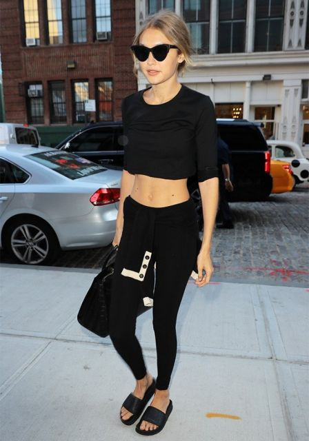 Gigi Hadid veste calça legging preta, blusa cropped, chinelo slide e bolsa no mesmo tom.