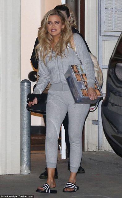 Khloe Kadarshian veste calça moletom cinza, casaco na mesma cor e chinelo slide preto.