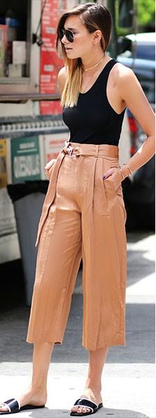 Modelo veste look com calça pantacourt na cor terra, blusa de alcinha e chinelo slide no mesmo tom.