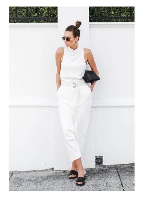 Modelo veste calça em alfaitaria branca, blusa de gola sem mangas e chinelo slide preto.
