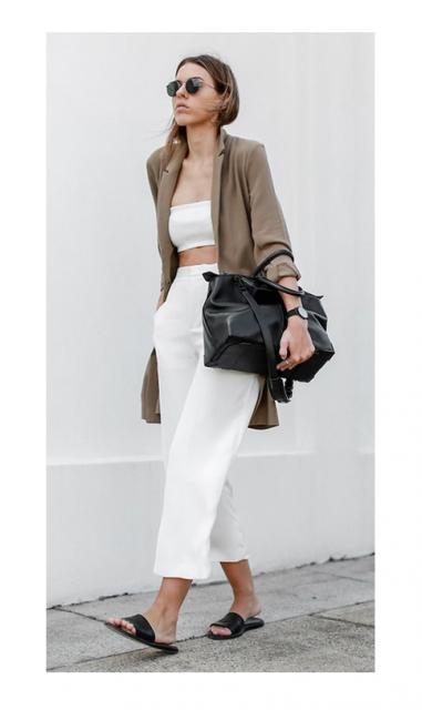 Modelo veste calça branca, top na mesma cor, casaquinho marrom, bolsa e chinelo slide em tom de preto.