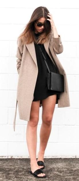 Look com vestido preto, casaco bege, bolsa e chinelo slide preto.