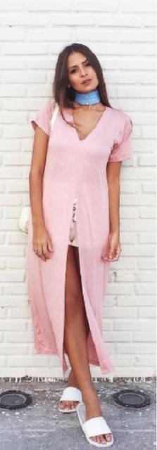 Modelo veste vestido longo larguinho com fenda, na cor rosa com chinelo slide branco.