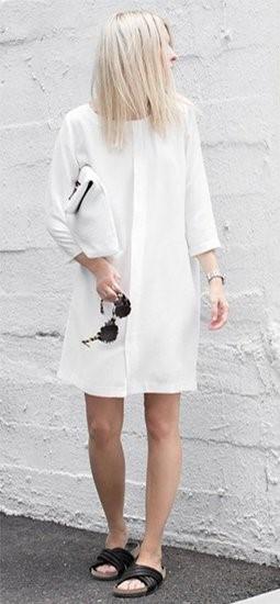 Modelo usa vestido larguinho curto, manga tamanho médio , na cor branca e chinelo slide preto.