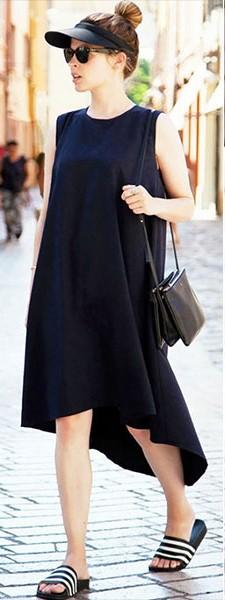 Look com vestido tamanho médio regata, na cor preto, bolsa no mesmo tom e chinelo slide listrado em tons de preto e branco.
