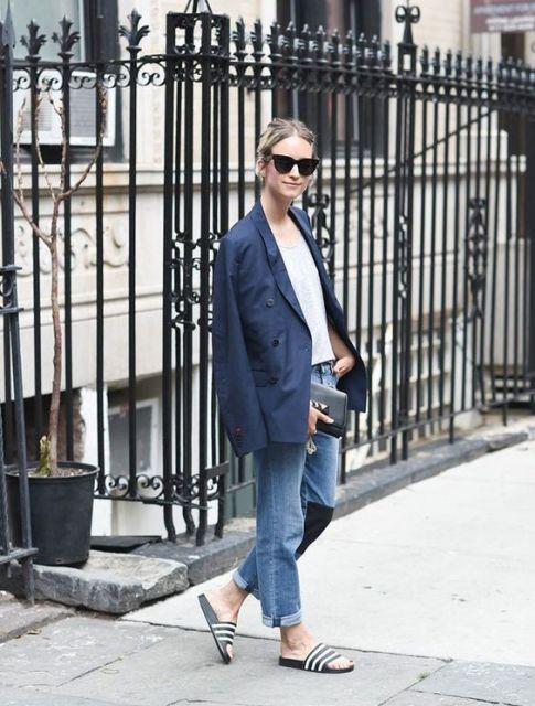 Modelo veste calça jeans, blusa branca,blazer na cor azul e chinelo slide na cor preta.
