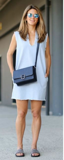 Modelo veste vestido larguinho azul claro, bolsa azul e chinelo slide listrado em preto e branco.