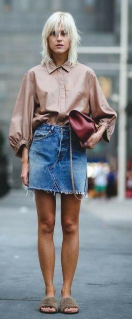 Modelo usa saia jeans azul com camisa em tons bege escuro, slide no mesmo tom e bolsa vermelha.