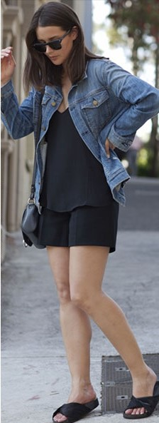 Look com conjunto de short e blusa em alfaiataria na cor preta, bolsa de ombro e chinelo slide no mesmo tom e jaqueta jeans.