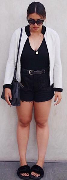 Modelo veste blusa e short na cor preta, casaquinho branco com preto e chinelo slide e bolsa no mesmo tom.