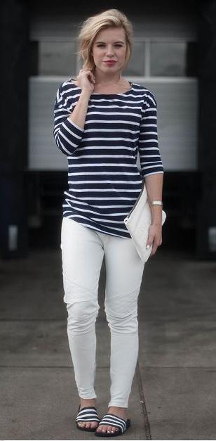 Modelo veste calça branca, blusa listrada nas cores preto e branco e chinelo slide na mesma cor e bolsa de mão branca.
