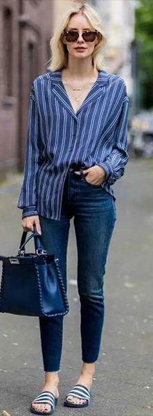 Look com calça jeans, camisa listrada azul e chinelo slide listrado.