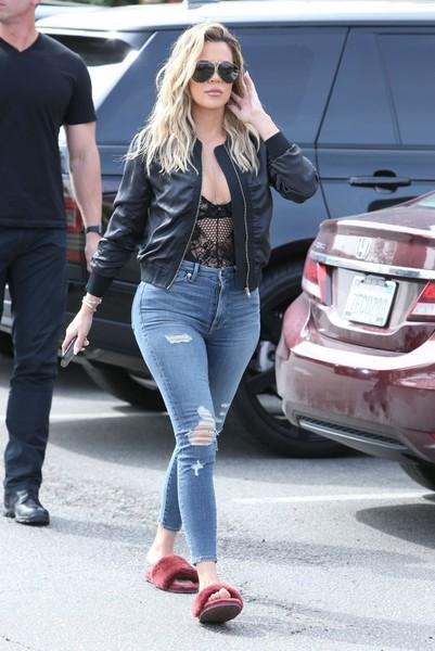Khloe Kadarshian veste calça jeans, blusa de renda, jaqueta preta em couro e chinelo slide preto de pelinhos.