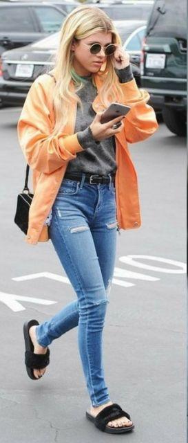 Moça veste calça jeans destroyed, blusa cinza, jaqueta laranja, bolsa de ombro preta e chinelo slide na mesma cor.