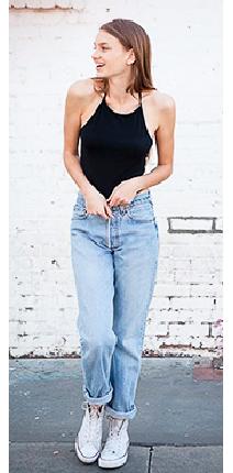 Modelo com cropped preto com calça jeans e tênis branco.