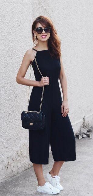 Macacão preto de alfaiataria, bolsa de ombro pequena e tênis branco.