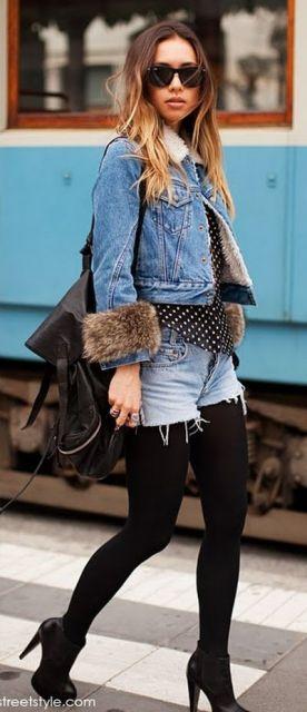 Modelo veste short jeans com meia preta, sapato de salto, blusa estampada e jaqueta jeans com detalhe de pelinhos.