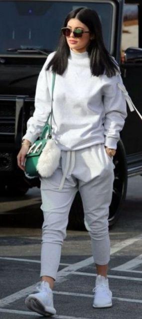 Kylie Jenner veste conjunto cinza de moletom, tênis branco e bolsa de ombro verde.