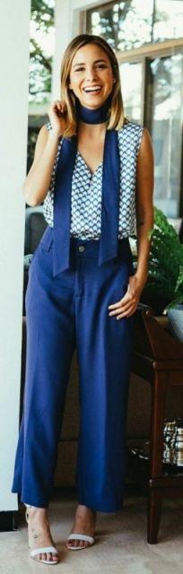 Luisa Accorsi veste calça azul e blusa em tom azul claro e sandália branca.