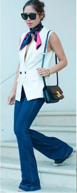 Look com colete branco, calça flare jeans e bolsa de ombro preta.
