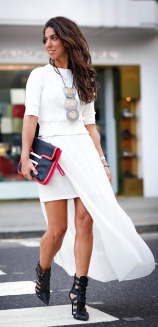 Modelo veste vestido branco, sapato preto elaborado e bolsa de mão preta com vermelho.