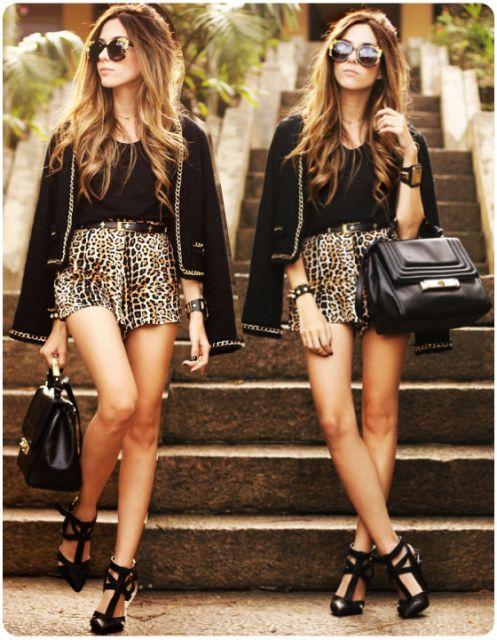 Modelo veste, blusa e jaqueta preta, short saia animal print e sapato preto elaborado.