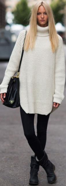 Suèter branco, calça preta, bota preta cano curto e bolsa de ombro.
