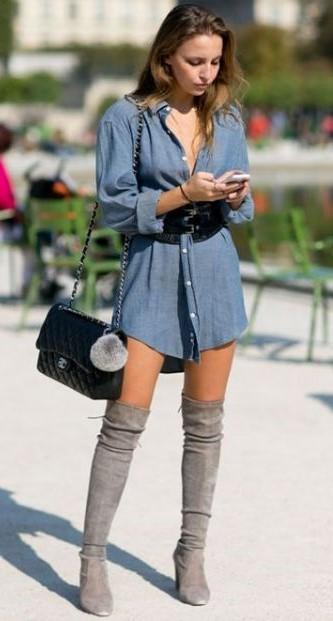 modelo veste camisa jeans comprida, bota cinza cano alto e bolsa de ombro preta.