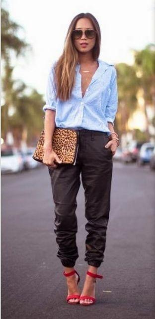Modelo veste calça estilo moletom preta, camisa de alfaiataria azul, sandália vermelha e bolsa de mão animal print.