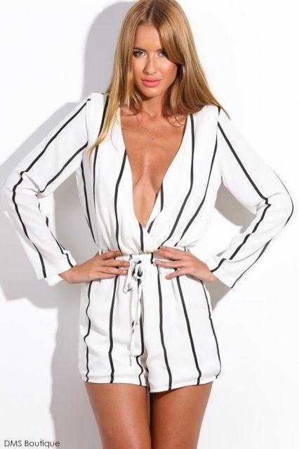 Modelo veste macaquinho branco com listras na cor preta e cordão ajustado a cintura.