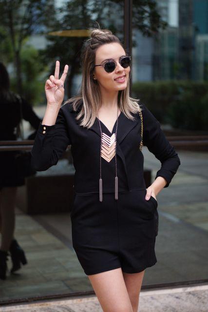 Modelo veste macaquinho simples na cor preta, óculos escuros e colar.