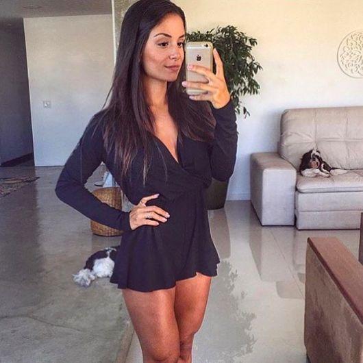 Modelo veste macaquinho preto simples com decote médio.
