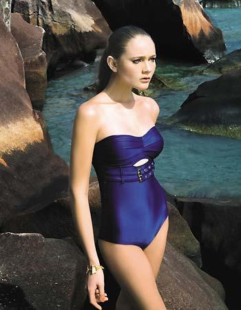 Modelo veste maiô toma que caia na cor azul cintilante.