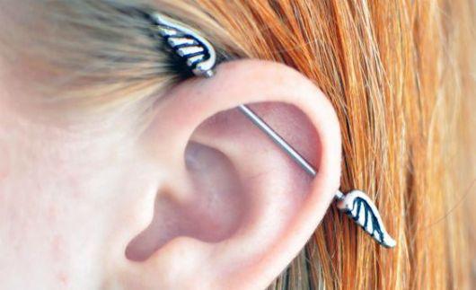 Piercing com fecho no formato de asas.