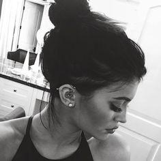 Mulher com piercing transversal na orelha.