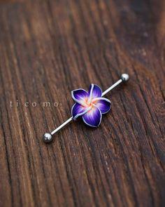 Piercing com flor no meio da haste.