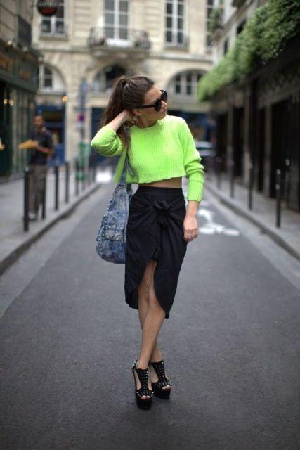 Blusa verde neon, saia preta com fenda.