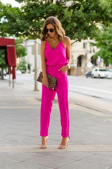 Modelo veste macacão longo rosa fluorecente.