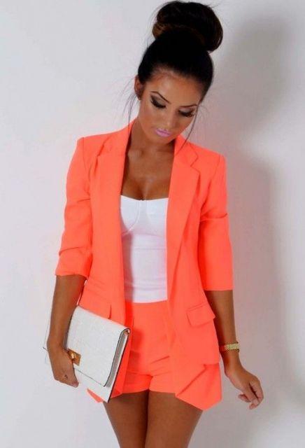 Look com blusa branca, blazer e bermuda flúor laranja.