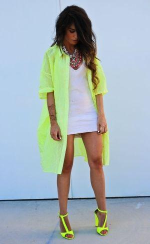 Modelo veste vestido branco, sobreposição verde neon e sandália da mesma cor.