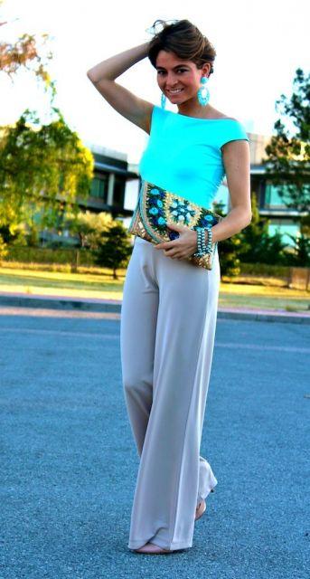 Modelo veste blusa neon azul, calça cinza e bolsa de mão.