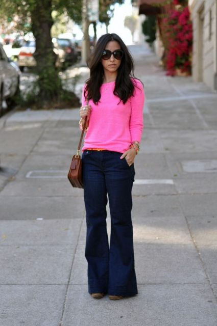 Blusa rosa neon, calça flare azul-marinho e bolsa marrom.